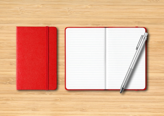 펜으로 빨간색 닫히고 열린 줄이 그어진 노트북. 나무 배경에 고립
