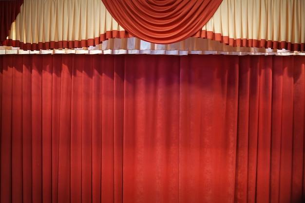 Красный закрытый занавес со светлыми пятнами в театре