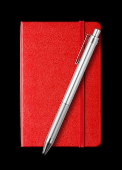 Red closed notebook and pen isolated on black