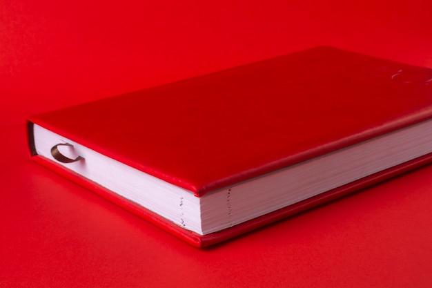 Красный закрытый блокнот на красном фоне
