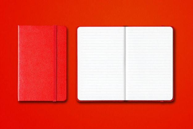 Red closed and open lined notebooks isolated