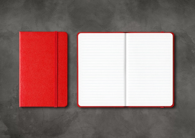 Red closed and open lined notebooks mockup isolated on dark concrete surface
