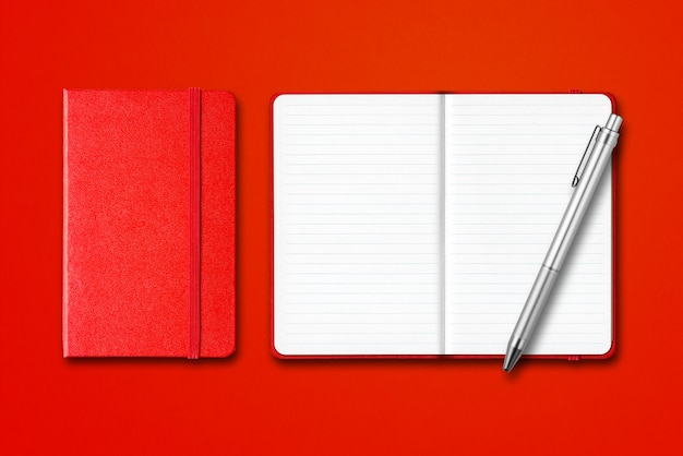Red closed and open lined notebooks with a pen isolated on colorful background