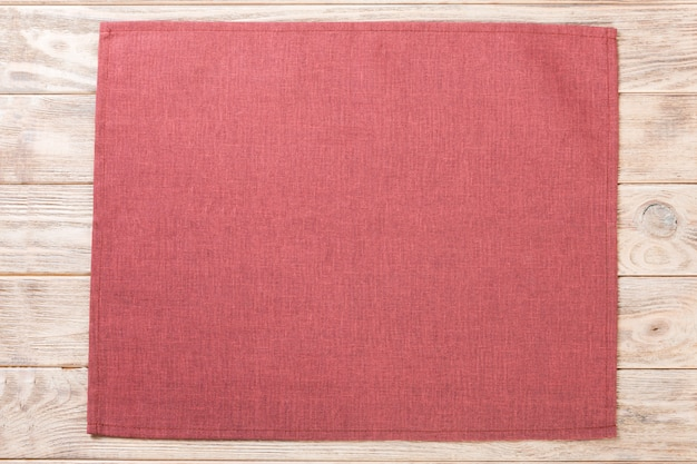 Red cloth napkin on brown rustic wooden