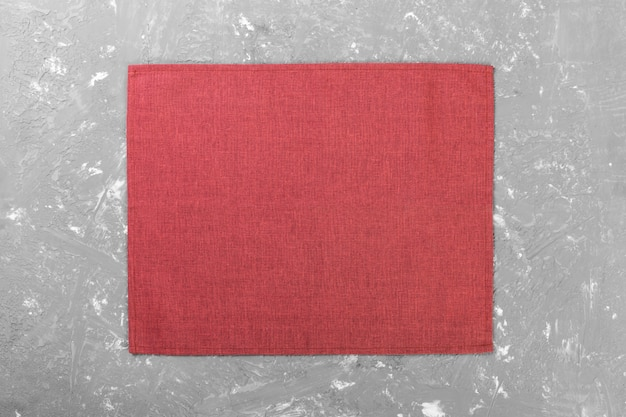 Red cloth napkin on rustic cement surface