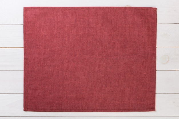 Red cloth napkin on white rustic wooden  top view with copyspace