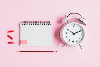 Red clothes peg; spiral notepad; rubber; pencil and alarm clock against pink backdrop
