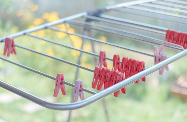 Red clothespin hanging at laundry rack