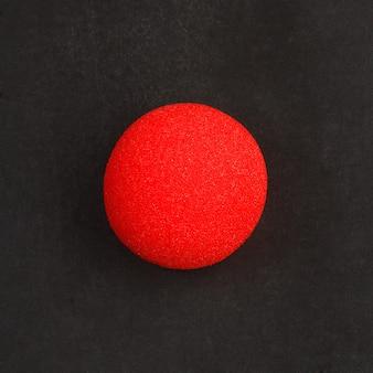 黒の黒板の背景に赤いピエロの鼻