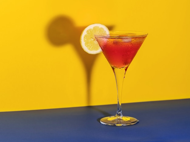 Red cocktail in a glass shaping its shadow with a lemon slice