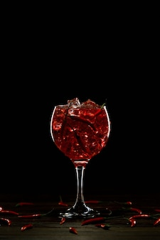 Red cocktail in a glass with ice and chili peppers valentines day concept