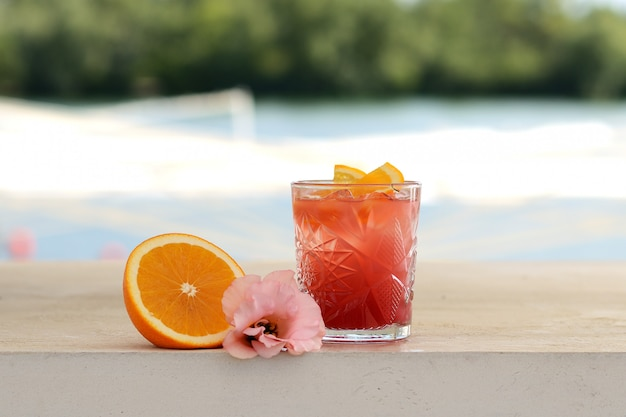 Red cocktail in a glass with a slice of orange. with flower decor