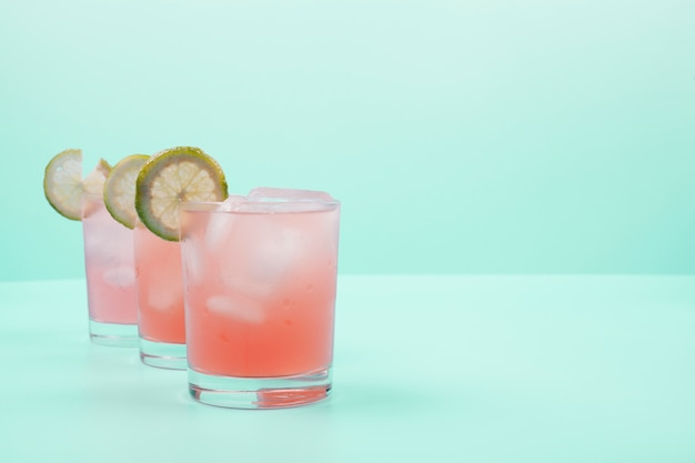 Red cocktail glasses with lemon slices and ice cubes on mint background