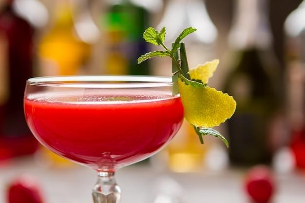 クーペグラスの赤いカクテル。レモンの皮のかけら。クローバークラブの作り方。フレッシュジュースとシロップ。