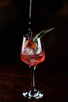 Red cocktail with ice and cherry in a transparent glass. liquid pouring into a glass