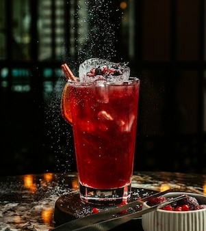 Red cocktail with ice cubes and berries.