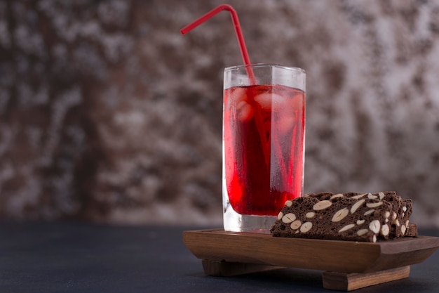 Red cocktail with ice cubes in a glass with a slice of cake aside