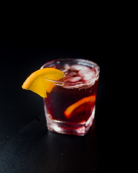 Red cocktail with ice cubes and lemon slices.