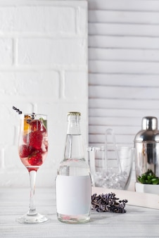 Red cocktail with ice and strawberry,  lavender with a bottle of tonic on the bottle on wooden background