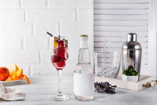 Red cocktail with ice and strawberry,  lavender with a bottle of tonic on the bottle