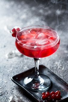 Red cocktail with ice vapor.