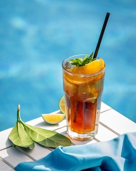 Red cocktail with lemon, orange slices and hreen herbs by a pool.
