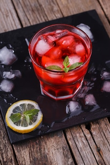 Red cocktail with mint and ice,