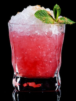 Red cocktail with mint leaves isolated on black