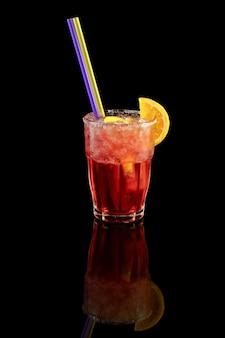 Red cocktail with orange slice, summer cold drink over black background