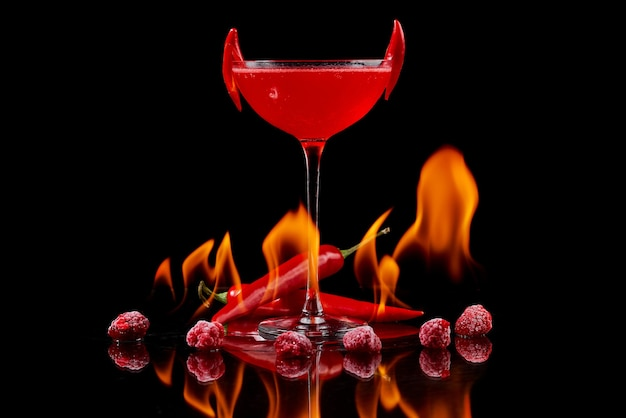 Red cocktail with raspberries and searing pepper on the mirror with flames of fire. high quality photo