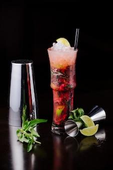 Cocktail rosso con fette di limone, menta e cubetti di ghiaccio.