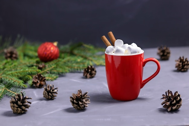 マシュマロとシナモンスティックスプルースブランチコーンとクリスマスボールと赤いココアマグ