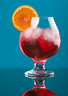 Красный коктейль с ледяными детенышами на синем фоне.