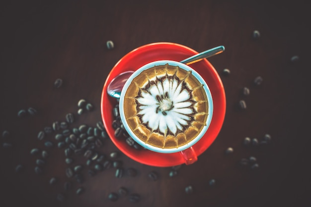 Red coffee cup decorated with coffee beans on the table