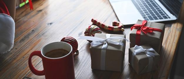 赤いコーヒーカップ、ラップトップコンピューター、木製のテーブルにクリスマスプレゼント。