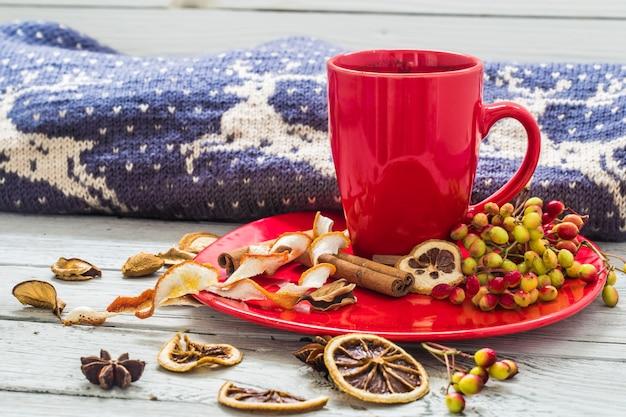 プレート、木製のテーブル、飲料の赤いコーヒーカップ。