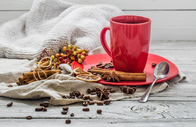 Red coffee cup on a plate, wooden table, beverage.