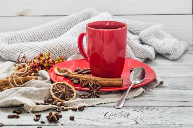Tazza di caffè rosso su un piatto, parete in legno, bevanda