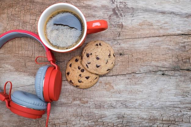 나무 테이블에 레드 커피 컵, 빨간 헤드폰 및 초콜릿 칩 쿠키. 위에서 볼 수 있습니다. chirstmas 개념으로 커피입니다.