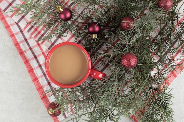 Red coffee cup on tablecloth with christmas balls and pine branch