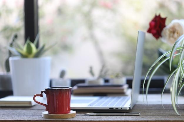 側面図のラップトップと木製のテーブルの植木鉢と赤いコーヒーカップ