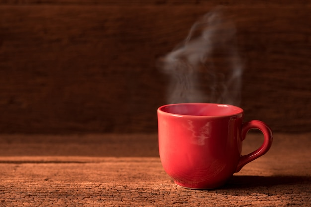 Red coffee cup with smoke stream on wooden table under moring sunlight