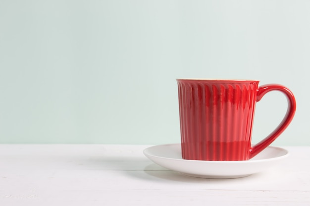 Red coffee cup on wooden table over pastel green background