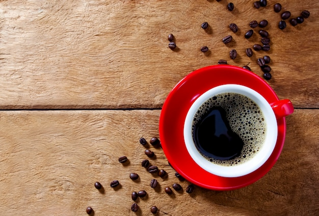 Red coffee cup on wooden table with coffee beads. background with coffee beans