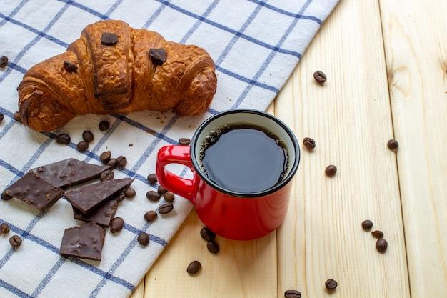 木製の背景に赤いコーヒーマグカップとクロワッサン。上からの眺め。コーヒー豆とチョコレート