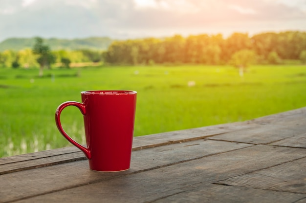 Red coffee mug rests on the balcony with beautiful rice fields.