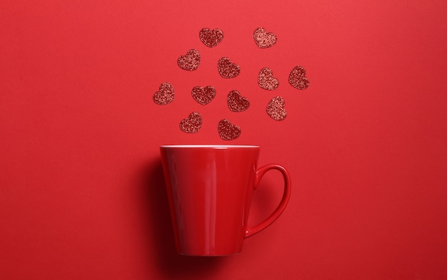Red coffee mug with red glitter hearts on red wall. flat lay composition. romantic, st valentines day concept.