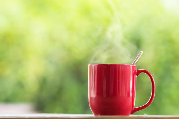 Red coffee mug on wooden tabletop against grunge green blur background