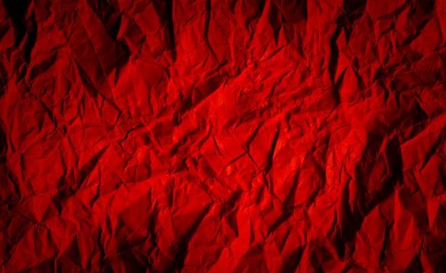 暗いしわ紙による赤い色の抽象的な背景テクスチャ