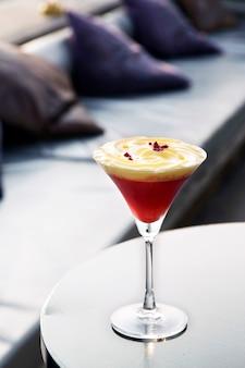 ホイップクリームによる赤い色のカクテルのトッピングをテーブルに